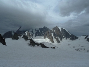 Blick vom Dent du Géant Richtung Glacier du Géant. Links in der Sonne die Tour Ronde, rechts der Grand Capucin und hinten in den Wolken der Mont Blanc