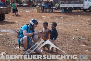 Flo zeigt Kindern in einem Dorf die Bilder, die er von ihnen gemacht hat