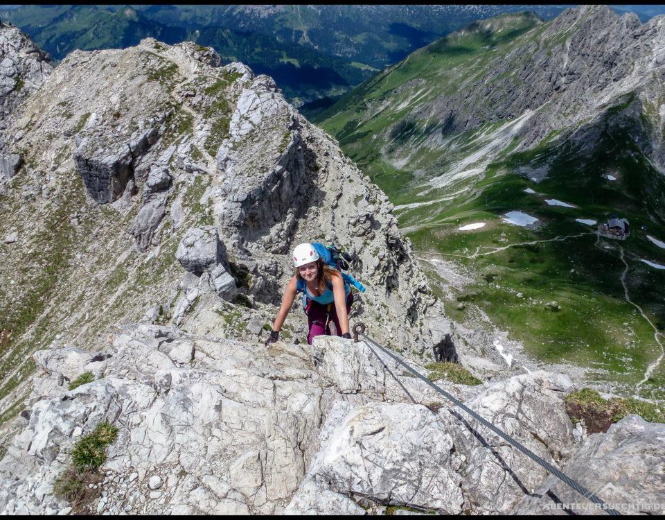 Elena unterwegs auf dem Mindelheimer Klettersteig. Im Hintergrund die Fiderepaßhütte.